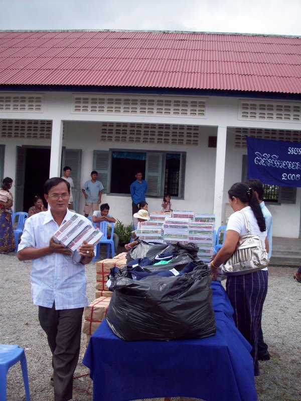 Village chief shares in distributing the exercise books